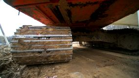 Primo piano di un cingolo del trattore a cingoli che guida in una palude Sparato dal grandangolo Movimento lento video d archivio