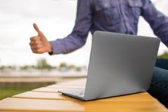 Primo piano di un computer portatile Computer portatile su un banco su un fondo vago Giovane che dà un pollice fino ad un compute immagini stock