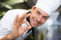 Primo piano di un cuoco maschio sorridente che gesturing segno giusto Fotografia Stock