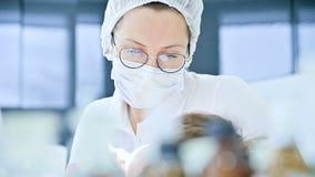 Primo piano di un dentista della donna che esamina la cavità orale di un paziente femminile all'età Alto lavoro professionale chi archivi video