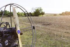 Primo piano di un'elica con un motore dell'motore-aliante contro lo sfondo di un campo immagini stock