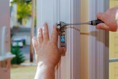 Primo piano di un fabbro professionista che installa o che ripara una nuova serratura di chiavistello senza molla di scatto fotografia stock