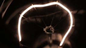 Primo piano di un filamento di tungsteno giallo Lisci l'aumento e la diminuzione nel potere video d archivio
