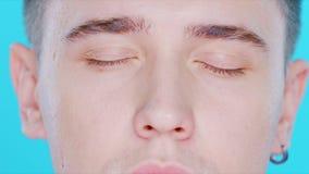 Primo piano di un fronte del tipo su un fondo blu Il suo allocco degli occhi archivi video