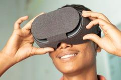 Primo piano di un giovane che avverte realtà virtuale tramite una cuffia avricolare di VR fotografia stock libera da diritti