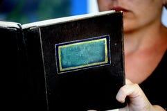 Primo piano di un libro o di un manu isolato senza il titolo con una persona che legge dietro sui precedenti - spazio per scriver immagini stock libere da diritti