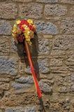 Primo piano di un mazzo dei fiori variopinti che pendono da una parete di pietra in un vicolo di Orvieto fotografia stock