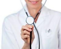 Primo piano di un medico femminile che mostra uno stetoscopio Fotografia Stock Libera da Diritti
