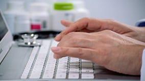 Primo piano di un medico maschio che per mezzo di una tastiera di computer archivi video
