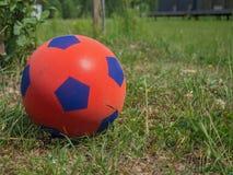 Primo piano di un pallone da calcio rosso per i bambini sull'erba verde davanti ad una casa di campagna Spazio per testo fotografia stock libera da diritti