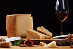 Primo piano di un parmigiano con bicchiere di vino Formaggio sulla scheda di legno Immagine Stock Libera da Diritti