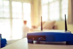 Primo piano di un router senza fili e di un giovane che per mezzo del computer portatile Fotografie Stock