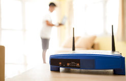 Primo piano di un router senza fili e di un giovane che utilizza computer portatile ed i computer portatili sul salone a casa con Fotografia Stock Libera da Diritti
