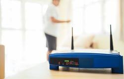 Primo piano di un router senza fili e di un giovane che utilizza computer portatile ed i computer portatili sul salone a casa con Fotografie Stock Libere da Diritti