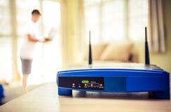 Primo piano di un router senza fili e di un giovane che utilizza computer portatile ed i computer portatili sul salone a casa con Immagini Stock