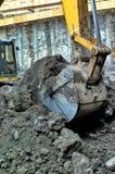 Primo piano di un secchio dell'escavatore che scava in terra Immagini Stock