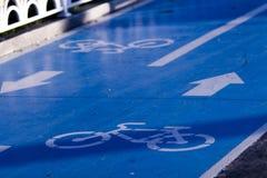 Primo piano di un segno dell'itinerario della bicicletta dentro due direzioni con il materiale blu, le frecce e le icone della co immagine stock
