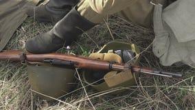 Primo piano di un soldato sovietico dalla seconda guerra mondiale che si siede sulla terra archivi video