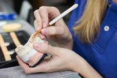 Primo piano di un tecnico dentario che applica porcellana ad una muffa immagini stock