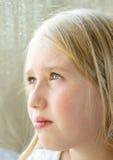 Primo piano di un teenager osservando fuori una finestra Fotografia Stock