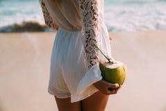 Primo piano di un telaio potato dalla parte posteriore La ragazza sta tenendo una noce di cocco fresca succosa matura con una rot immagine stock