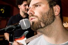 Primo piano di un tipo con un canto della barba su un microfono fotografia stock libera da diritti