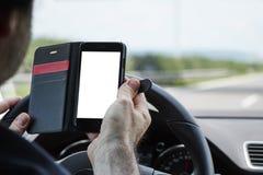 Primo piano di un uomo che conduce automobile e che tiene telefono cellulare in o anteriore immagini stock