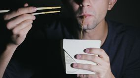 Primo piano di un uomo che sta mangiando le tagliatelle con i bastoncini da una scatola Alimento cinese di cibo europeo stock footage