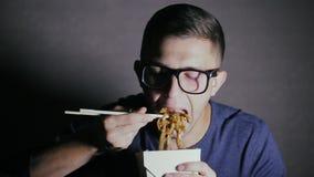 Primo piano di un uomo che sta mangiando le tagliatelle con i bastoncini da una scatola Alimento cinese di cibo europeo video d archivio