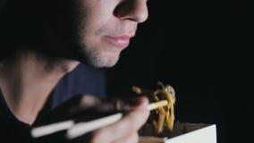 Primo piano di un uomo che sta mangiando le tagliatelle con i bastoncini da una scatola Alimento europeo di cibo archivi video