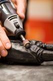 Primo piano di un uomo del hardworker che per mezzo di un lucidatore sopra una statua metallica su un fondo vago Fotografia Stock