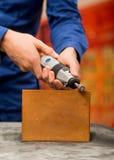 Primo piano di un uomo del hardworker che porta una maglietta blu e che utilizza un lucidatore in un pezzo di legno, su una tavol Fotografie Stock