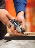 Primo piano di un uomo del hardworker che utilizza un lucidatore in una struttura di legno, su una tavola grigia in un fondo vago Fotografie Stock Libere da Diritti