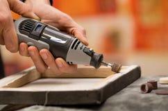 Primo piano di un uomo del hardworker che utilizza un lucidatore in una struttura di legno, su una tavola grigia in un fondo vago Fotografie Stock
