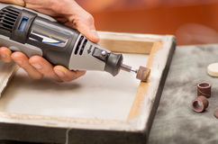 Primo piano di un uomo del hardworker che utilizza un lucidatore in una struttura di legno, su una tavola grigia in un fondo vago Immagini Stock Libere da Diritti