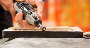 Primo piano di un uomo del hardworker che utilizza un lucidatore in una struttura di legno, su una tavola grigia in un fondo vago Fotografia Stock