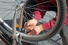 Primo piano di un uomo, facendo le riparazioni della bicicletta e mainte Immagini Stock