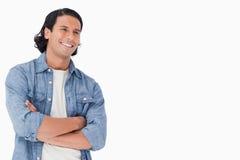 Primo piano di un uomo sorridente che attraversa le sue braccia Fotografia Stock