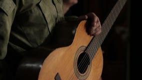 Primo piano di un uomo in uniforme militare che tiene una chitarra stock footage