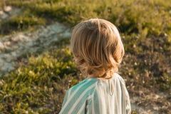 Primo piano di una bambina con la sua parte posteriore Ritratto di piccola ragazza bionda fotografia stock
