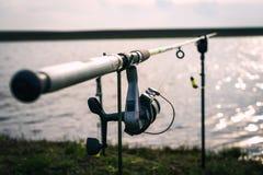 Primo piano di una bobina di pesca su una barretta vicino ad un lago Immagine Stock