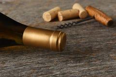 Primo piano di una bottiglia del vino di Chardonnay con la cavaturaccioli e dei sugheri su una tavola di legno rustica immagini stock libere da diritti