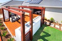 Primo piano di una casa e di un patio lussuosi con le colonne di legno e la b Immagine Stock Libera da Diritti