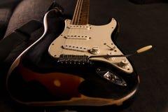 Primo piano di una di una chitarra elettrica colorata di sprazzo di sole coperta di pittura nera rimossa a determinati punti per  fotografia stock libera da diritti