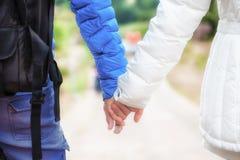 Primo piano di una coppia felice in tog tenentesi per mano e di camminata di amore Immagini Stock
