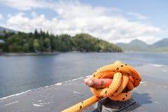 Primo piano di una corda di attracco con un'estremità annodata legata intorno ad un morsetto su un traghetto immagini stock