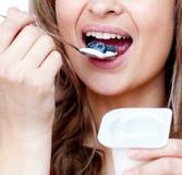 Primo piano di una donna che mangia un yogurt Immagine Stock Libera da Diritti