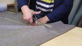 Primo piano di una donna più anziana in una fabbrica della mobilia che sta tagliando un materiale grigio per il sofà archivi video