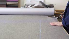 Primo piano di una donna più anziana in una fabbrica della mobilia che sta tagliando un materiale grigio per il sofà video d archivio