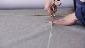 Primo piano di una donna più anziana in una fabbrica della mobilia che sta tagliando un materiale grigio per il sofà stock footage